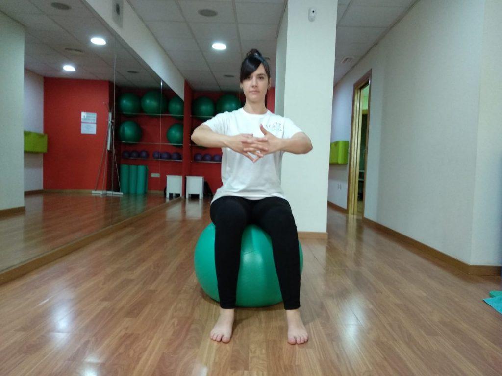 Rotación de tronco entrelazando las manos en posición sentada