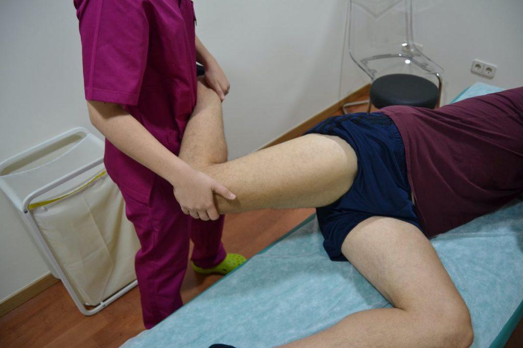 Estiramiento aplicando fisioterapia deportiva sobre la pierna del deportista