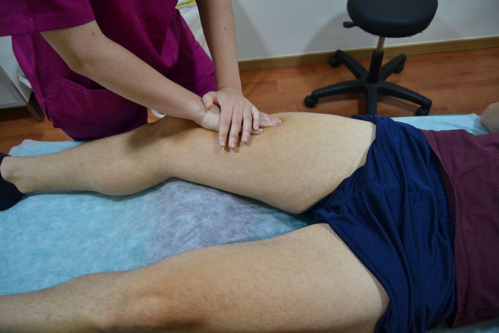 Tratamiento con fisioterapia deportiva sobre cuádriceps del paciente